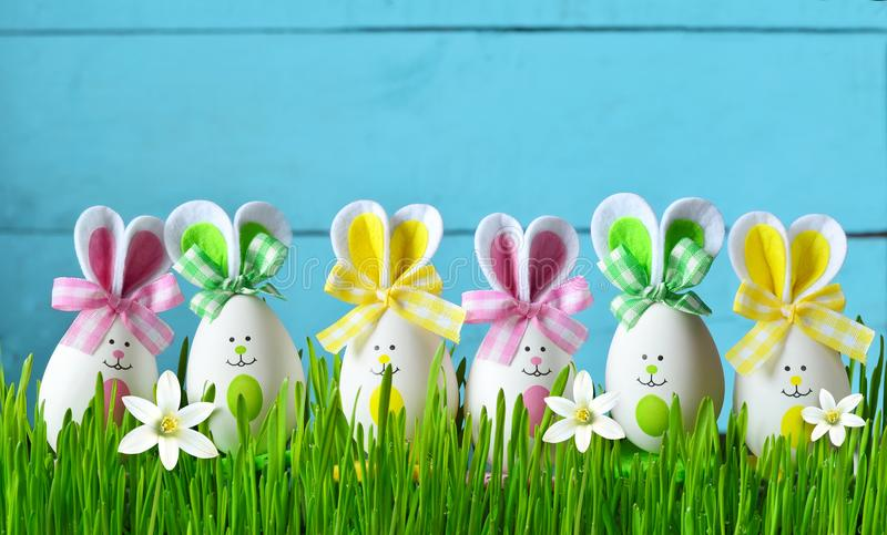 Easter funny bunny on green grass with easter eggs and flowers. Easter background. Easter funny bunny on green grass with flowers and easter eggs. Easter stock photos