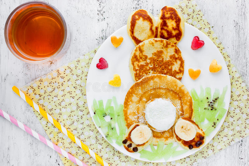 Easter funny bunny pancakes for breakfast. Easter funny bunny pancakes with fruit. Creative breakfast for kids of pancakes, kiwi, banana, apple and juice on a royalty free stock image
