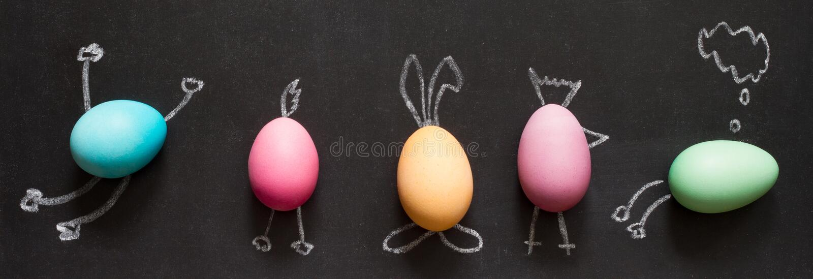 Easter funny painting eggs on blackboard abstract children`s background. On black royalty free stock photos
