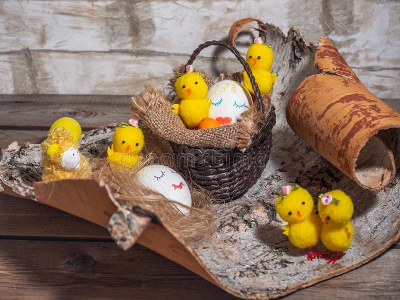 Easter funny picture with painted faces on the eggs. Toy Chicks stock photography