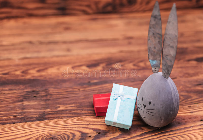 Easter gifts and a cute grey egg with bunny ears royalty free stock photo