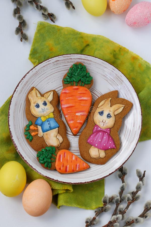 Easter gingerbread bunnies are located in a plate on white background, top view stock images