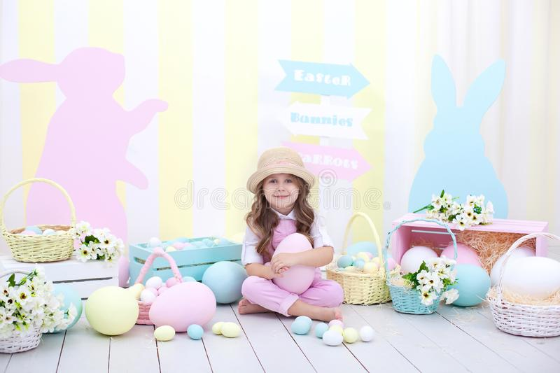 Easter! A girl holding a large colorful egg on the background of Easter interior. A cute baby is chasing Easter eggs. Easter and s stock photography