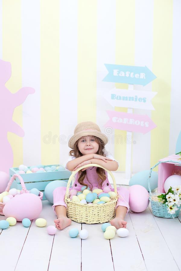 Easter! A girl holds a basket of eggs on the background of Easter interior. Easter colorful decor. Girl chasing Easter eggs. sprin royalty free stock photo