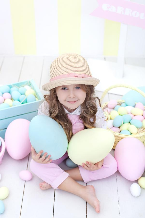 Easter! girl holds big multi-colored eggs in her hands against the background of the Easter interior. A cute baby is chasing Easte royalty free stock image