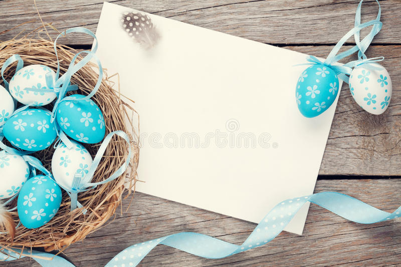 Easter greeting card with blue and white eggs in nest over wood royalty free stock photography