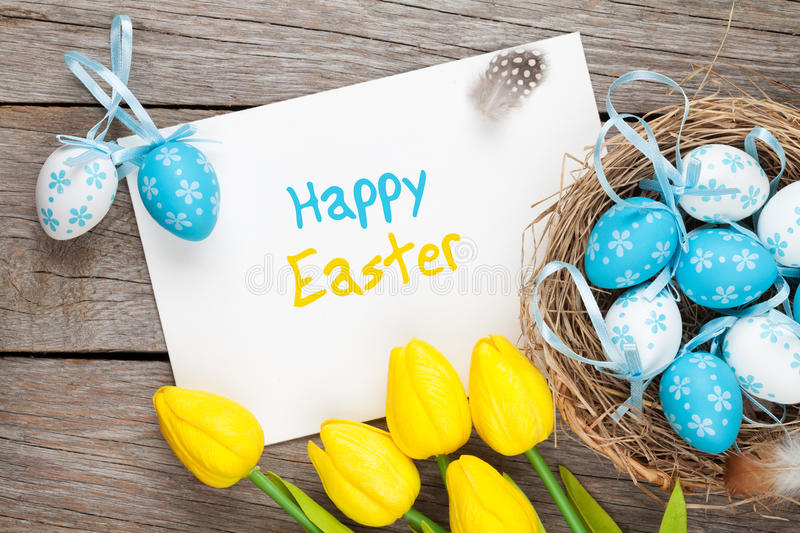 Easter greeting card with blue and white eggs and yellow tulips. Over wood. Top view with copy space royalty free stock photos