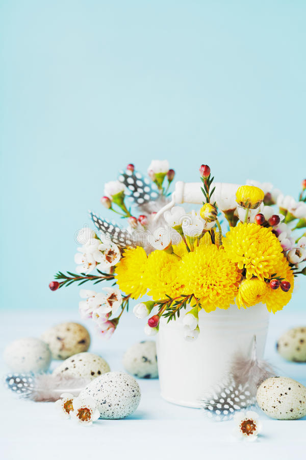Easter greeting card with colorful flowers, feather and quail eggs on blue background. Beautiful spring composition. stock photo
