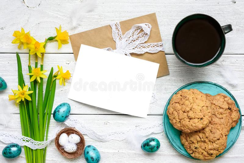Easter greeting card with easter eggs, spring flowers, cup of coffee and cookies for breakfast stock photography