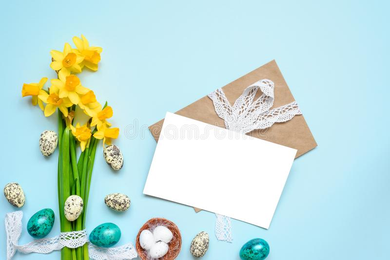 Easter greeting card with easter eggs and spring flowers mock up over blue background. mock up stock photo