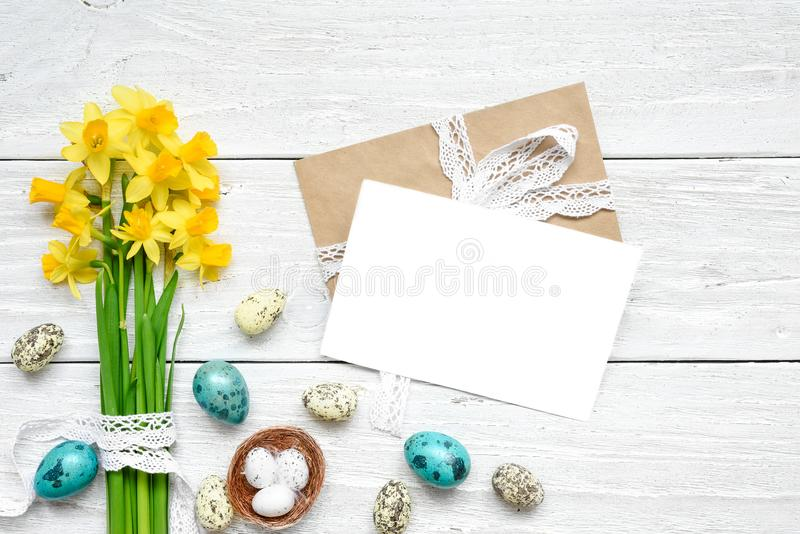 Easter greeting card with easter eggs and spring flowers mock up over white wooden table stock image