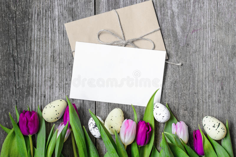 Easter greeting card with eggs and purple tulips royalty free stock photography