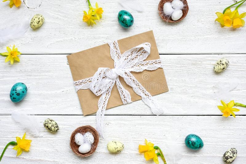 Easter greeting card with envelope in frame made of quail eggs, spring flowers and feathers stock photography