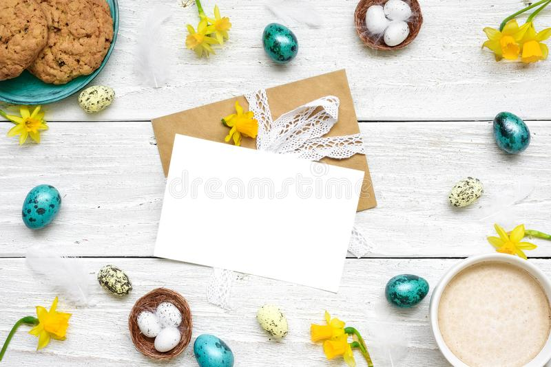 Easter greeting card in frame made of quail eggs, cup of cappuccino, spring flowers and biscuits royalty free stock image