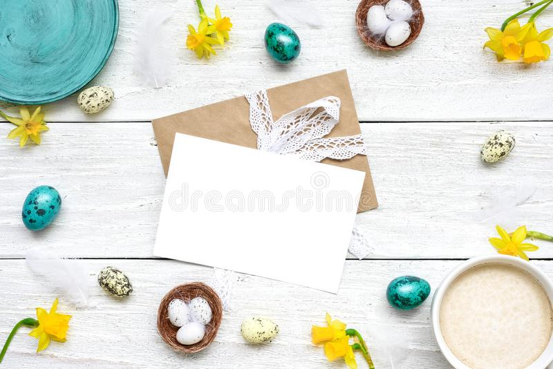 Easter greeting card in frame made of quail eggs, cup of cappuccino and spring flowers on white wooden background royalty free stock image