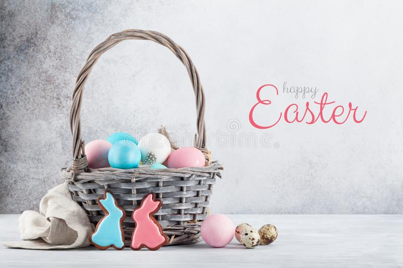Easter greeting card. With gingerbread cookies and colorful easter eggs in basket in front of stone wall stock photos