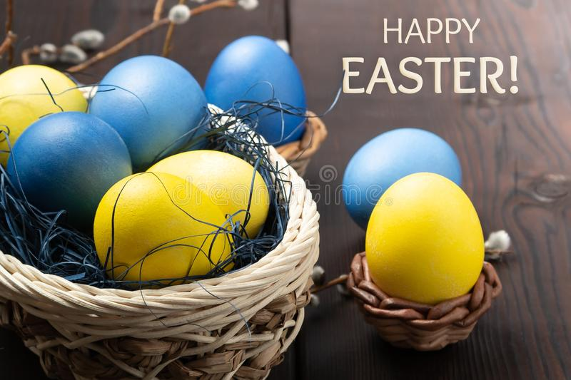 Easter greeting card - several colored eggs in a basket and on a dark wooden table with pussy-willow twigs and the royalty free stock photos