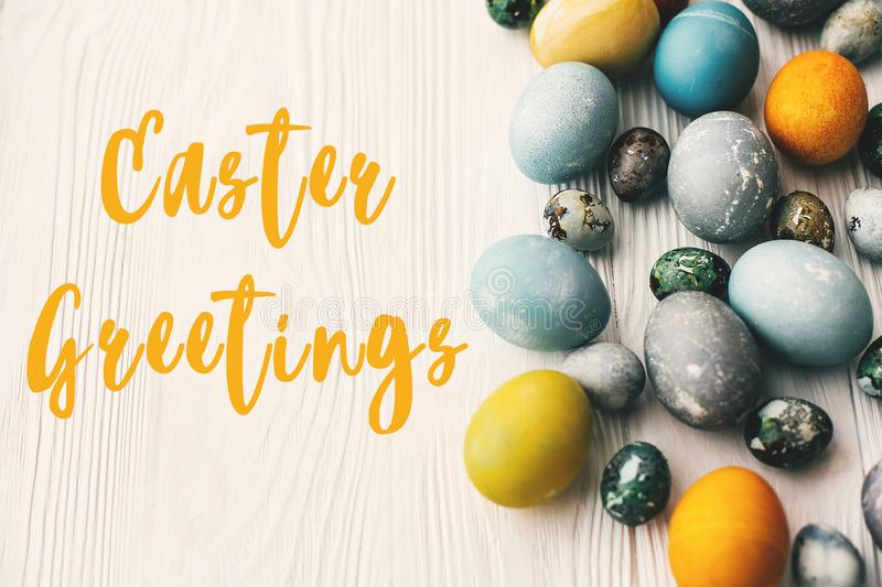 Easter Greetings text sign on stylish easter eggs on white wooden table. Modern easter eggs painted with natural dye in blue, grey. Yellow marble color. Happy stock illustration