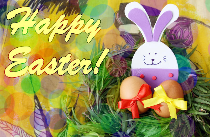 Easter hand made decorated greeting card: yellow eggs and hand made festive plastic foam bunny in green grass twigs nest on yellow stock photos