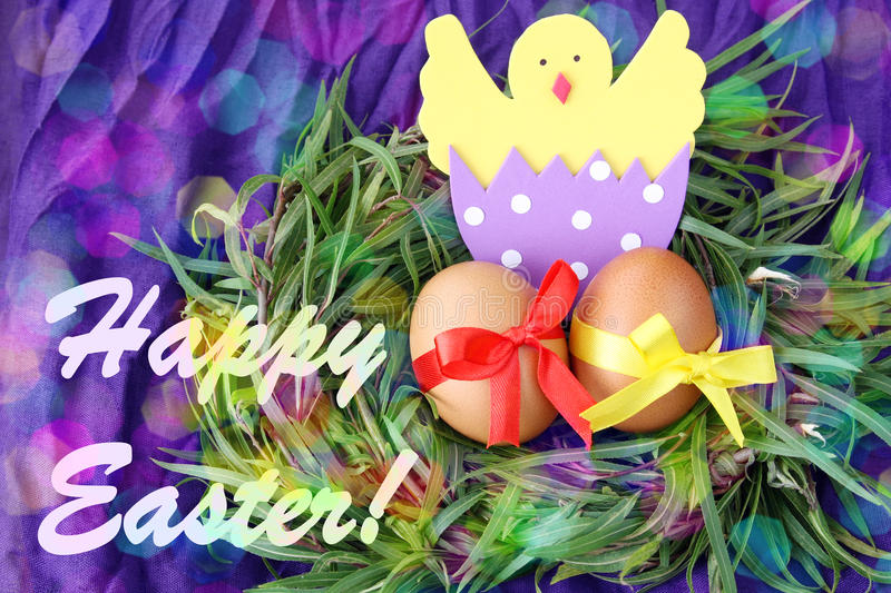 Easter hand made decorated greeting card: yellow eggs and hand made hatched chicken in eggshell in green grass twigs nest on purpl stock photo