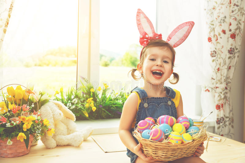 Easter. happy child girl with bunny ears and colorful eggs sitting at window in flowers. Easter. happy child girl with bunny ears and colorful eggs sitting at stock images
