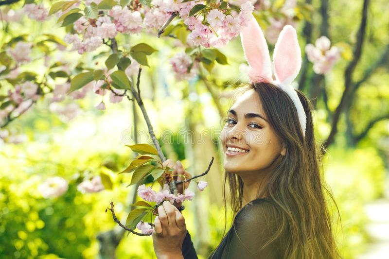Easter happy woman smiling at tree with blossoming sakura flowers royalty free stock photo