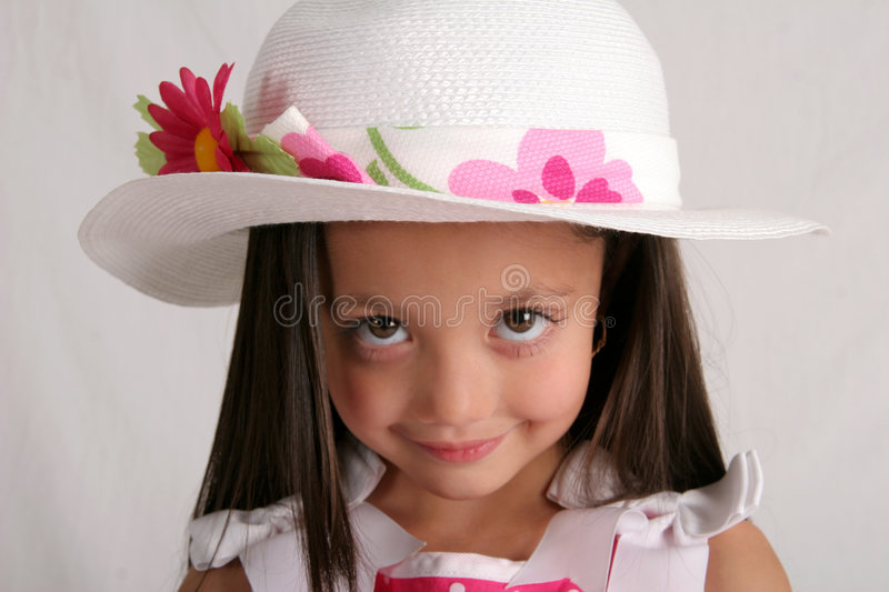 Easter hat. Wide-eyed young girl with fancy spring hat on royalty free stock photography