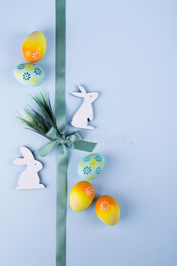 Easter holiday background with colorful painted chicken eggs decorative wooden bunny and flowers and ribbon. Flat lay royalty free stock image