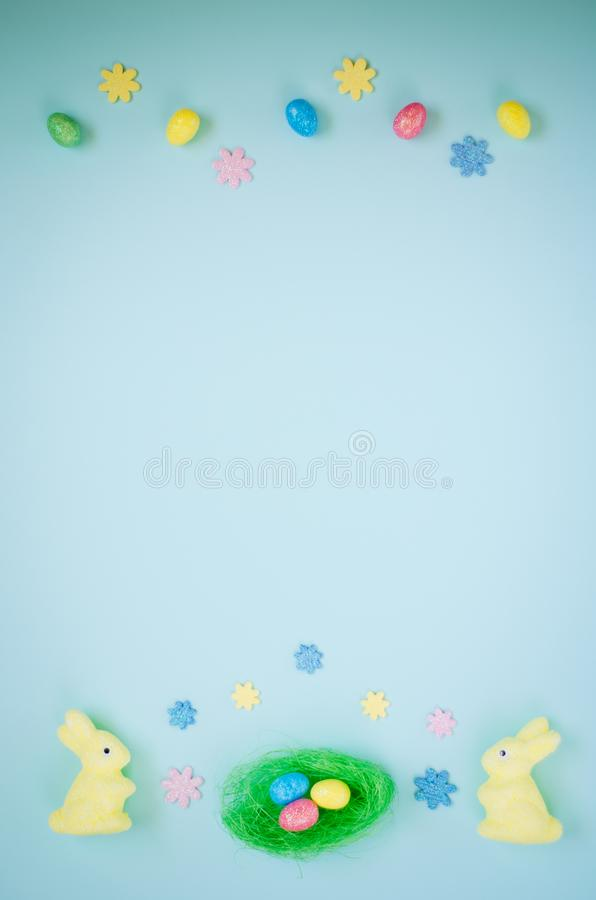 Easter holiday background with colorful shiny eggs, two yellow bunnies with flowers stock photos