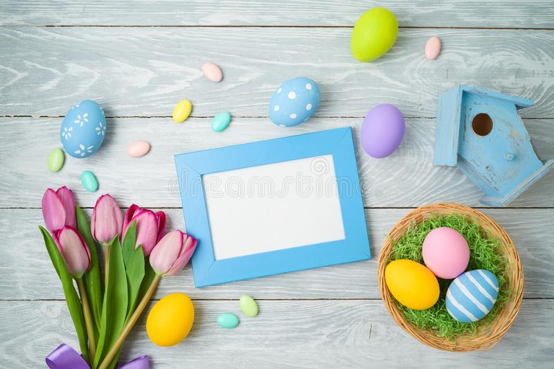 Easter holiday background with easter eggs in basket, photo frame and tulip flowers on wooden table. Top view from above royalty free stock photos