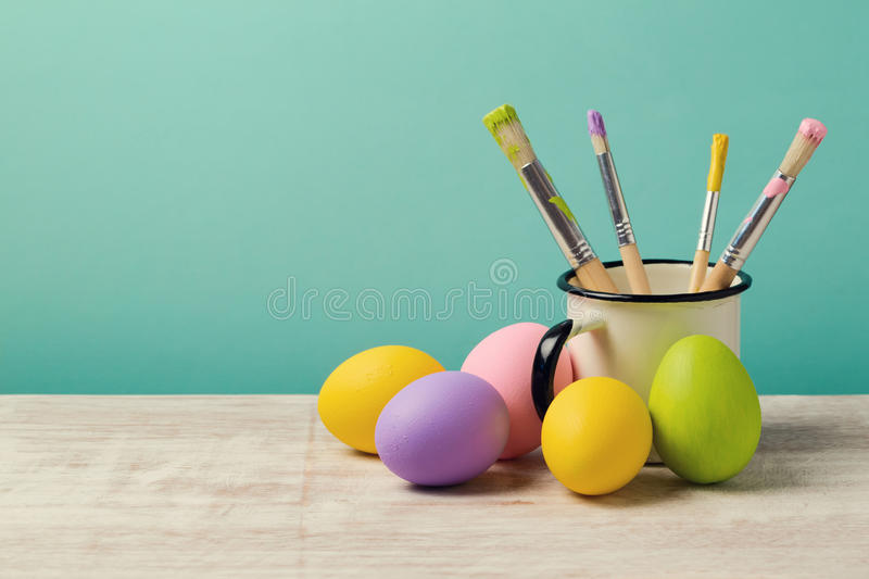 Easter holiday background with handmade painted eggs and brushes royalty free stock photo