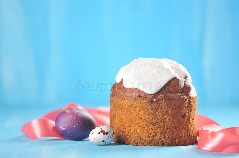 Easter holiday background. Painted eggs on a blue background and Easter cake stock photo
