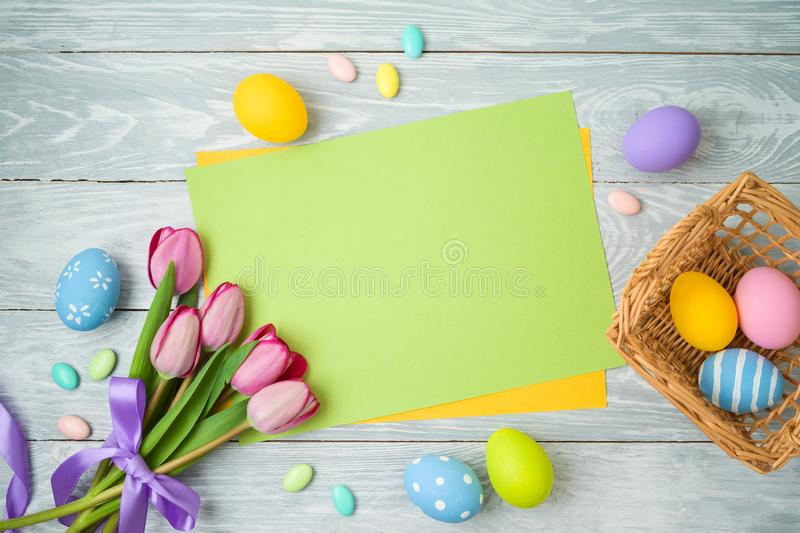 Easter holiday background with paper note, easter eggs in basket and tulip flowers on wooden table. Top view from above stock photography
