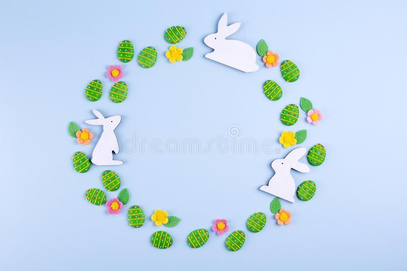 Top view of green sugar candy eggs, wooden bunny plased in a round frame on blue background. Flat lay, top view, copy space stock photos