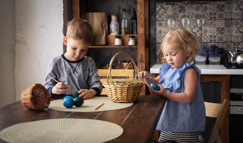 Easter holiday: children girl and boy paint colored eggs with tassels in the kitchen. European interior. stock photos