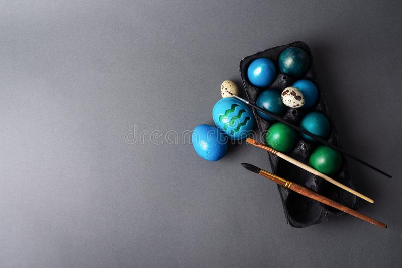 Easter holiday: colored painted eggs in a black box and a brush against a dark background. Top view royalty free stock images