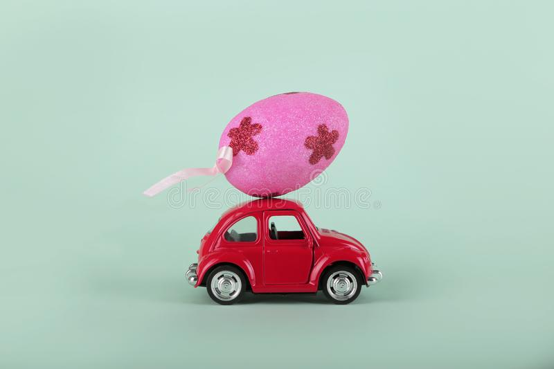 Easter holiday concept with egg on toy red car on turquoise background. Easter holiday concept with egg on toy red car on turquoise background stock images