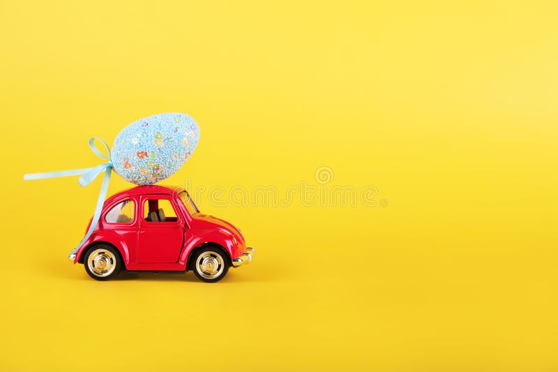 Easter holiday concept with egg on toy red car on turquoise background. royalty free stock images