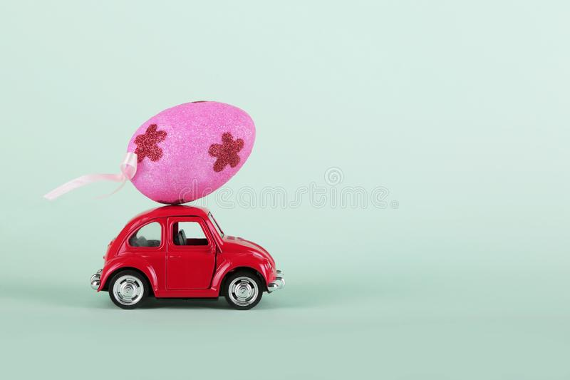 Easter holiday concept with egg on toy red car on turquoise background. stock photo