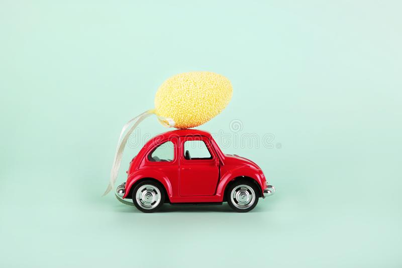 Easter holiday concept with egg on toy red car on turquoise background. royalty free stock image