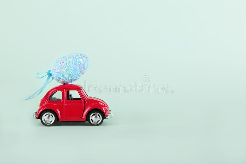 Easter holiday concept with egg on toy red car on turquoise background. stock image