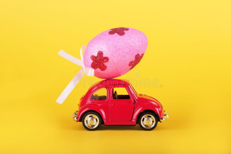 Easter holiday concept with egg on toy red car on yellow background. stock photos