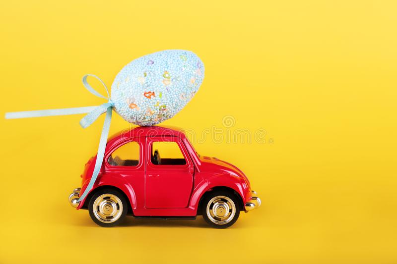 Easter holiday concept with egg on toy red car on yellow background. royalty free stock image