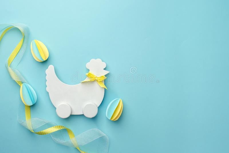 Easter holiday creative background with papercraft eggs, white wooden chicken hun on pastel blue table, trendy paper craft holiday stock photography