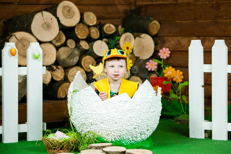 Easter holiday. A cute little girl in a duck suit hatched from a big egg. In the background a wooden stumps. Horizontally framed shot stock photo