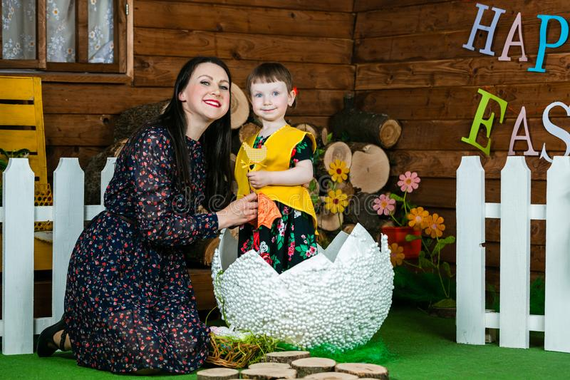 Easter holiday. A cute little girl in a duck suit hatched from a big egg. Mom hugs her daughter. On wall writing Happy Easter. Horizontally framed shot stock photos
