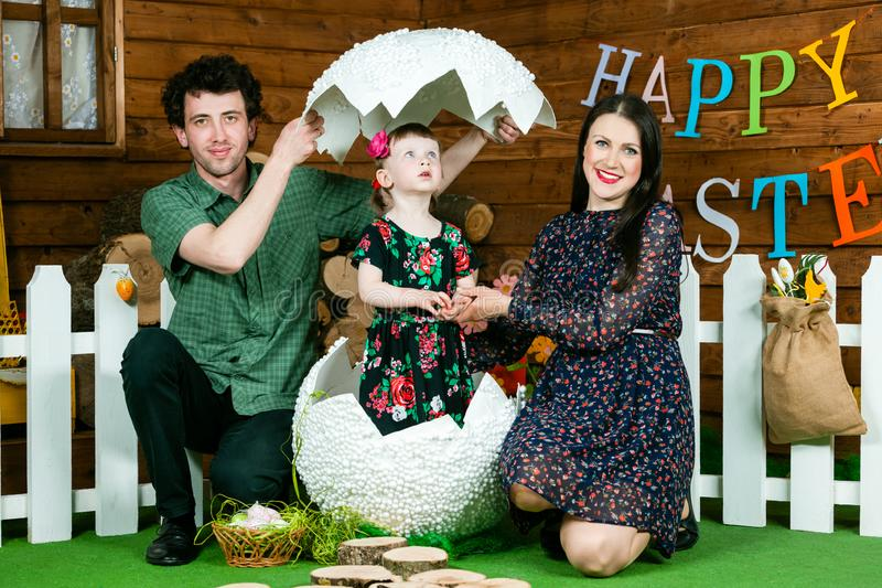 Easter holiday. A cute little girl hatched from a big egg. Near mom and dad. On the wall the writing happy Easter. Horizontally framed shot royalty free stock images