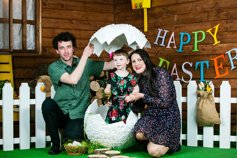 Easter holiday. A cute little girl hatched from a big egg. Near mom and dad. On the wall the writing happy Easter. Horizontally framed shot royalty free stock photography