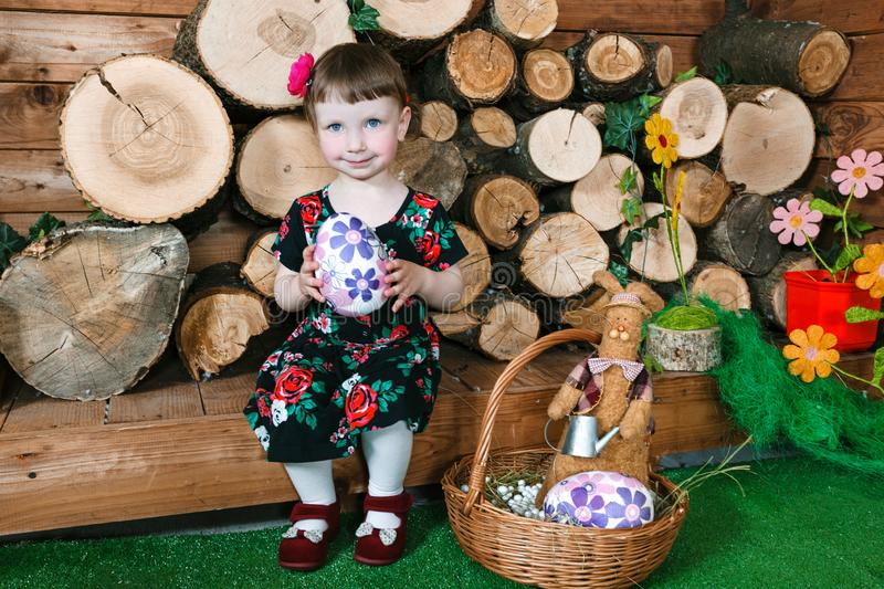 Easter holiday. Cute little girl holding an easter egg. In background a wooden stumps. Horizontally framed shot royalty free stock photos