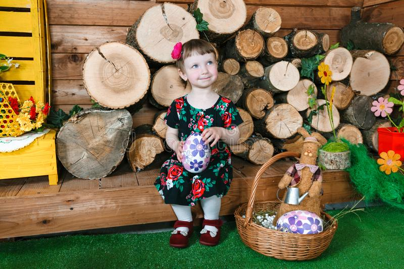 Easter holiday. Cute little girl holding an easter egg. In background a wooden stumps. Horizontally framed shot royalty free stock photo